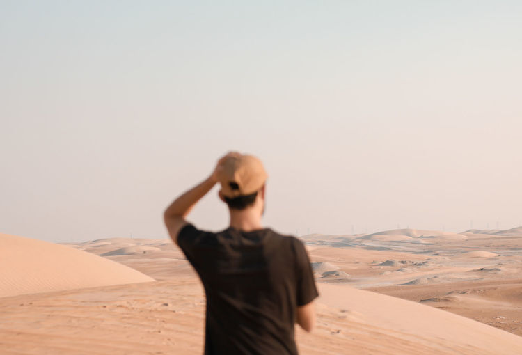 Young man on sand dune in desert against clear sky
