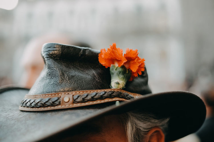Close-up of person wearing hat and flower