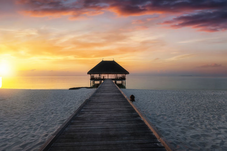 Sunset over a tropical beach with a wooden pier leading to a water lodge over the ocean Sky Sea Water Sunset Horizon Horizon Over Water Tranquility Pier Tranquil Scene Scenics - Nature The Way Forward Idyllic Beach Outdoors Cloud - Sky Tropical Climate Tropical Vacations Lodge House Villa Maldives Resort Wooden Ocean