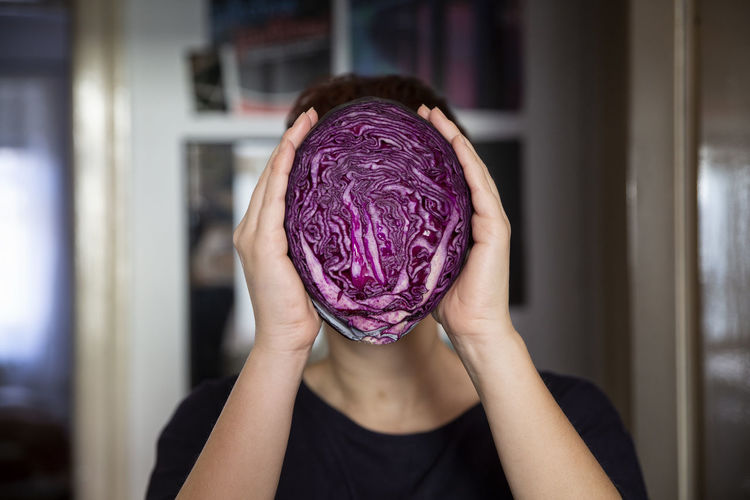Midsection of woman holding purple at home