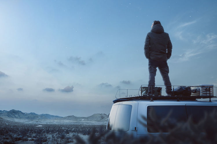 Traveler on top of his camper van enjoying a moonlit night. Sky Mode Of Transportation Nature Real People Transportation Standing Car Men One Person Rear View Travel Outdoors Beauty In Nature Solitude Campervan Van Camper Night Dark Tranquility View Scenics - Nature Adventure Roof Moonlight Thinking Contemplation