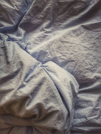 High Angle View Of Crumpled White Sheet On Bed