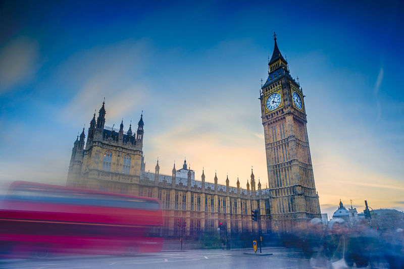 Blurred motion of double-decker bus on street by big ben against sky during sunset