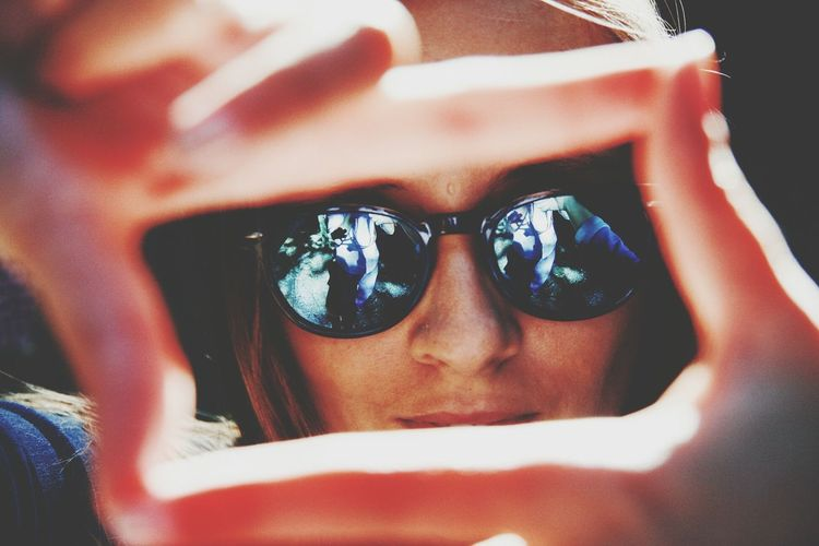 Close-Up Of Woman Wearing Sunglasses With Reflection Seen Through Finger Frame