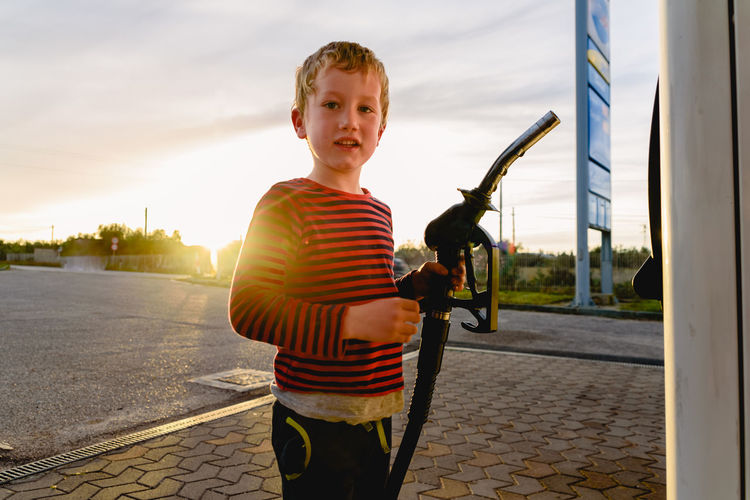 Portrait of boy holding fuel pump at gas station during sunset