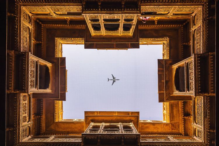 Directly below shot of airplane flying over palace in sky