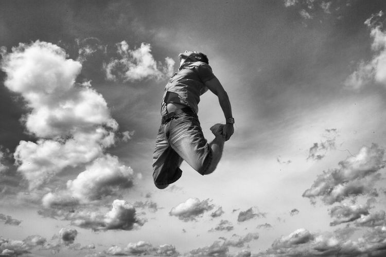 Low angle view of man jumping against cloudy sky