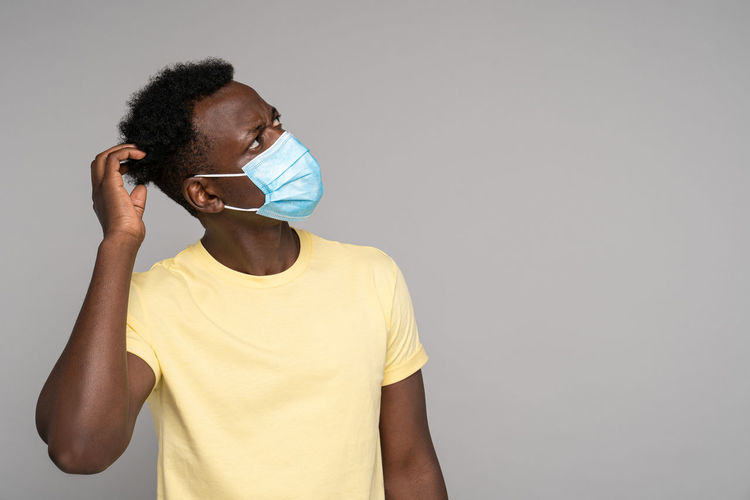 Afro-american man wear face mask, scratches her head and thinks, looking up at blank copy space