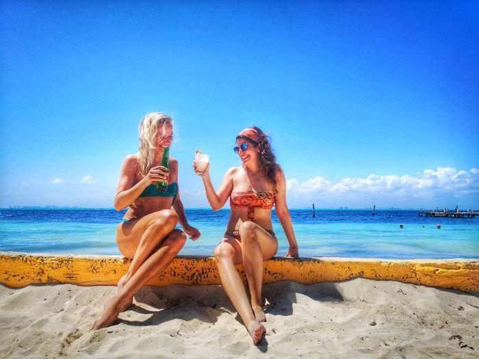 Friends enjoying at beach against sky