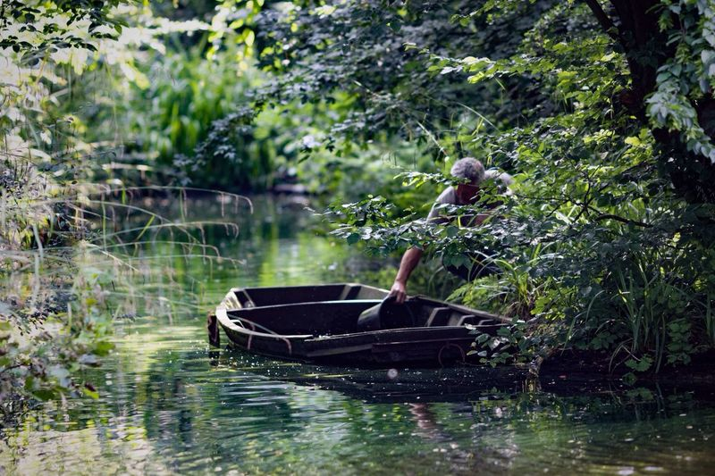 Man Collecting Water From Boat By Trees