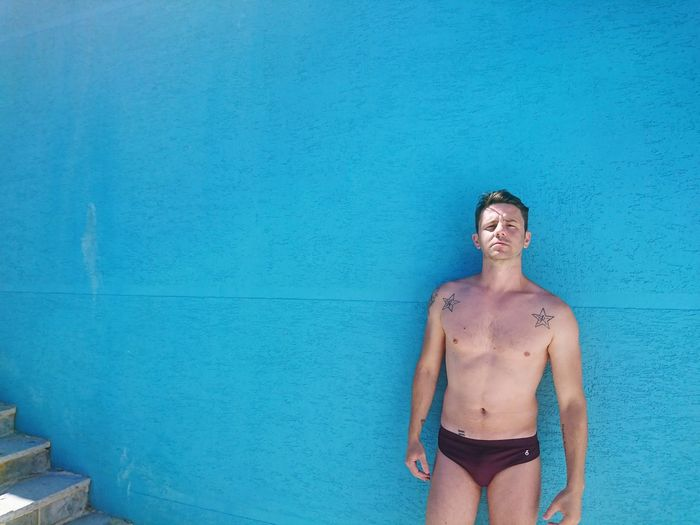 Portrait of shirtless man standing against blue wall