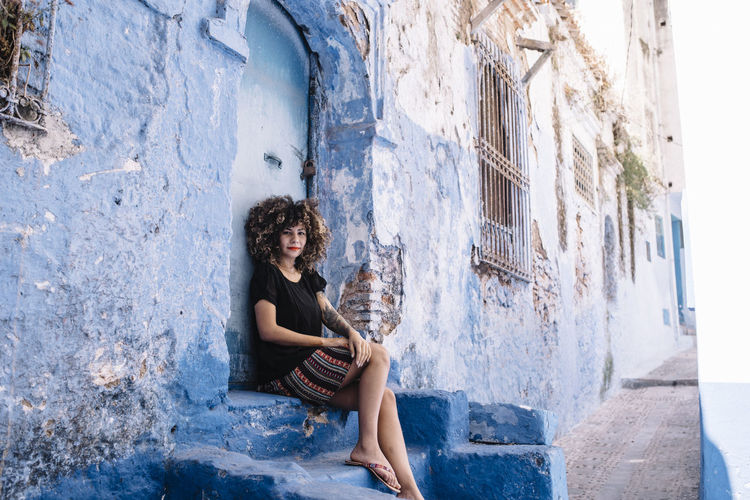 Portrait of young woman sitting by old house