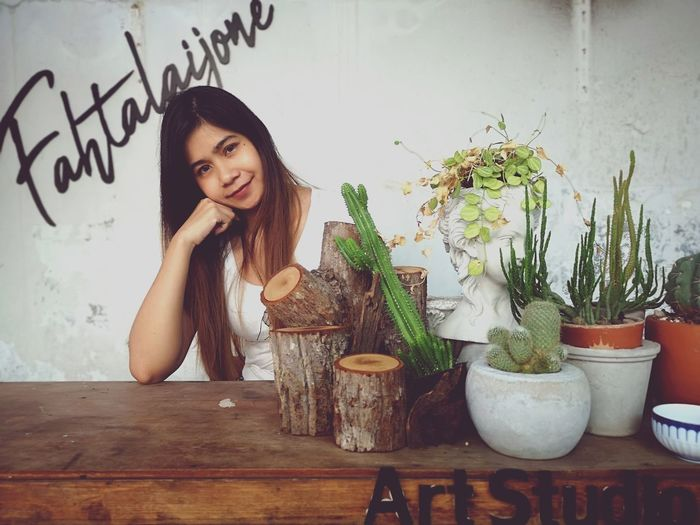 Portrait of young woman with potted plant on table