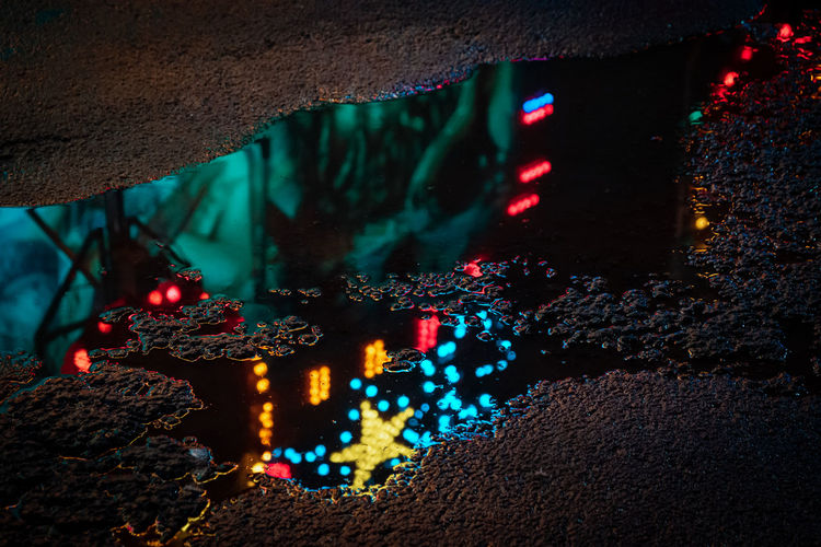 Lights of a fairground ride reflected in a puddle of rainwater at night.