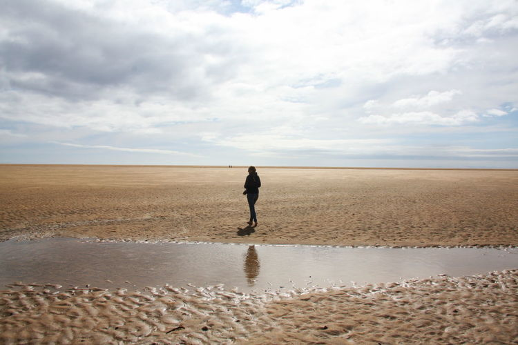Rear view of man walking on sand at beach