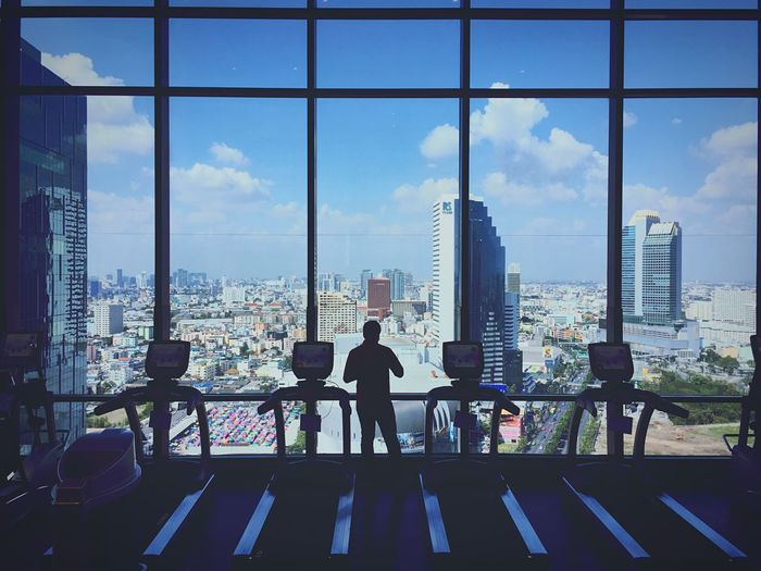 Exercise machines at gym with city view from its window