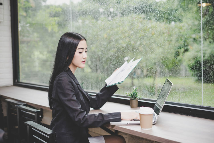 Businesswoman Reading Documents While Using Laptop At Desk In Office