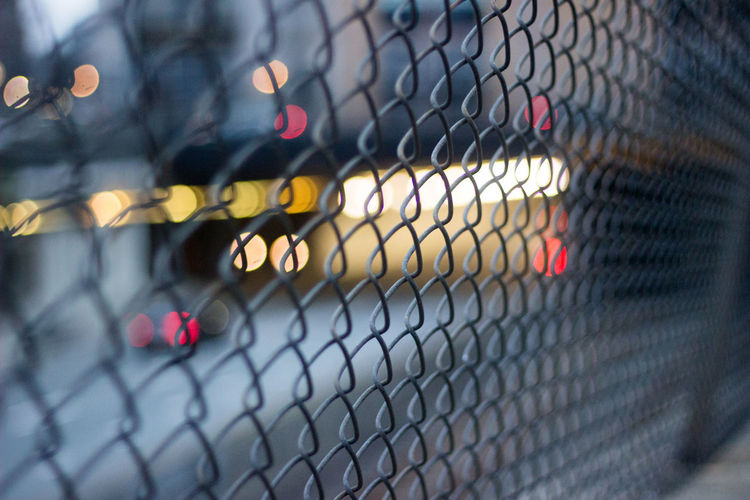 Chain Link Fence with traffic below, a beautiful bokeh of city colors. Car Lights City Cityscape Traffic Bokeh Chainlink Fence City City Lights City Night Lights Close-up Defocused Illuminated Metal Narrow Focus Night In The City Nightlife Outdoors Red Traffic Lights