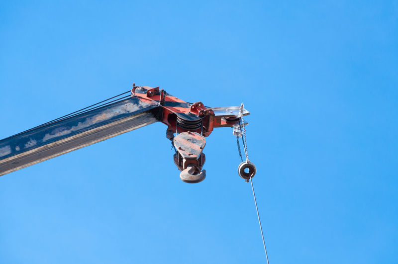 Low angle view of men on rope against clear blue sky