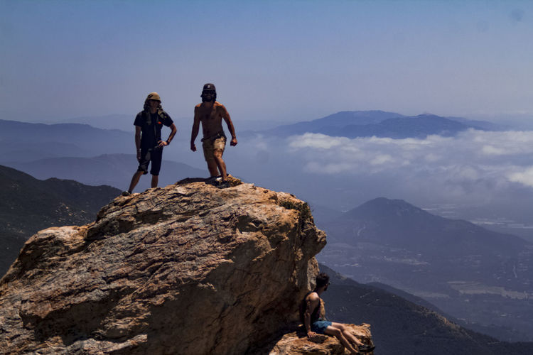 Friends on cliff against mountains