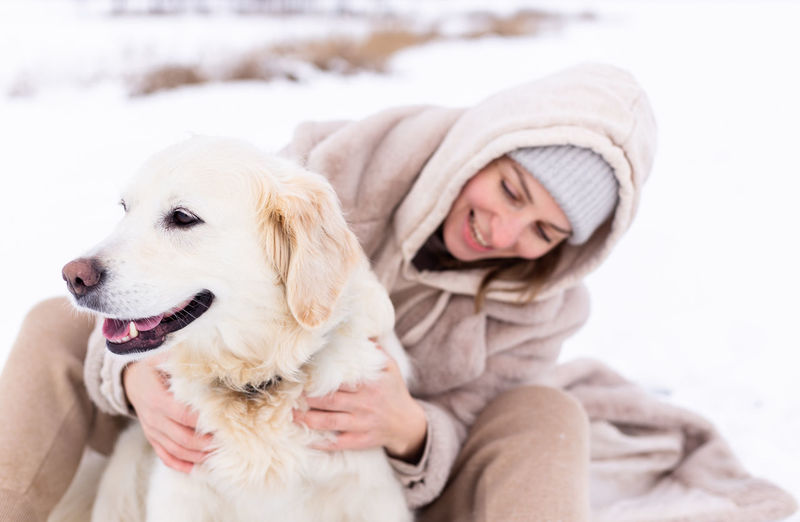Young woman with dog sitting in snow