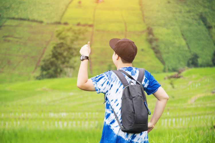 Rear view of boy gesturing thumbs up at rice paddy