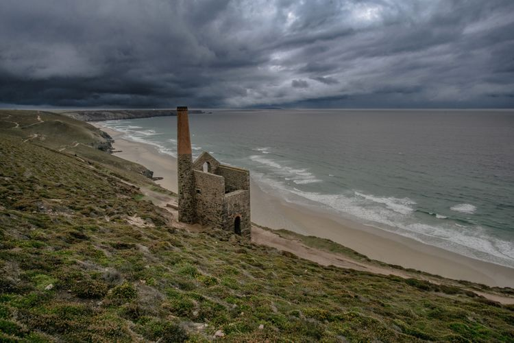 Stone building on hill by sea against cloudy sky