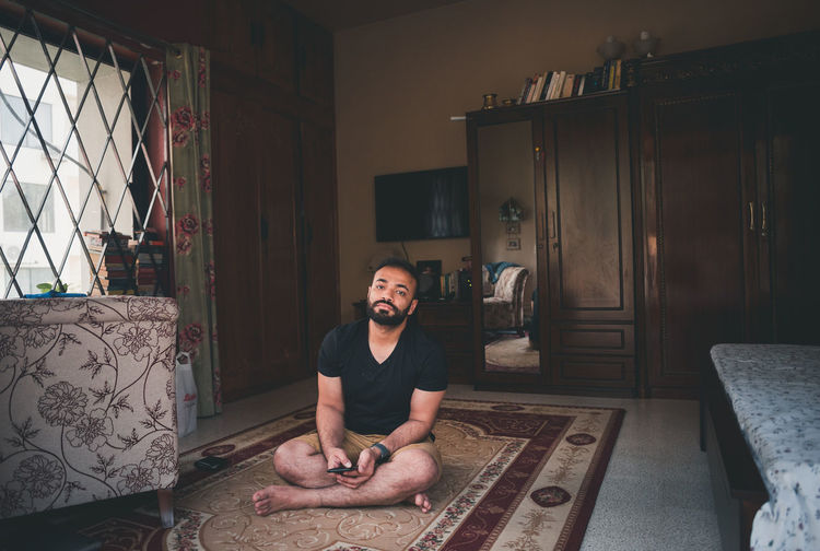 Portrait Of Young Man Sitting On Carpet In Living Room At Home
