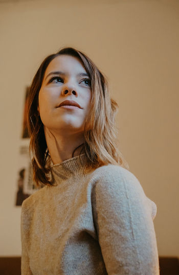 Portrait of a young woman against wall at home