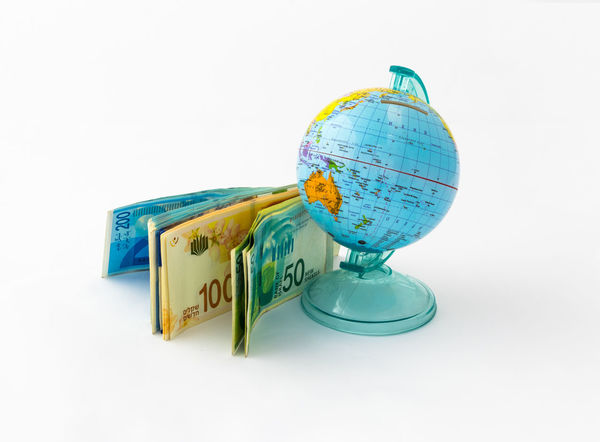 A money box made in the form of a globe, the planet Earth with a money slot at the top stands near a stack of Israeli banknotes of different value isolated on a white background. Business Currency Earning Earth Isolated Art Bank Banknote Buy Cash Coin Coins Design Exchange Finance Globe Israel Money Pay Planet Shekel Stock Studio Shot Wealth White Background