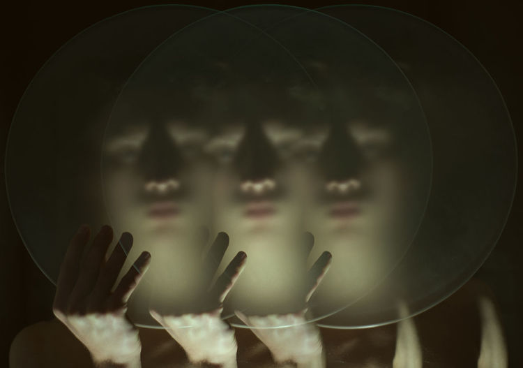 Multiple image of woman holding glass against black background