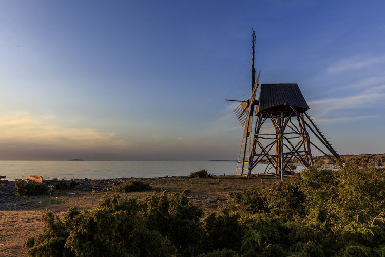 Traditional windmill by sea against sky during sunset