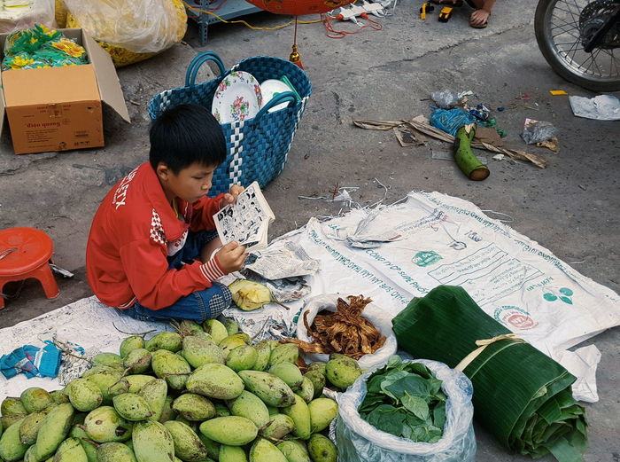 Boy reading book sitting by fruits for sale at market