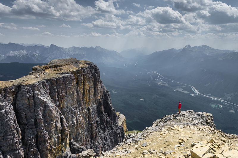 High angle view of man standing on cliff against mountains