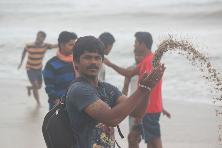 Portrait of man throwing sand while standing at beach