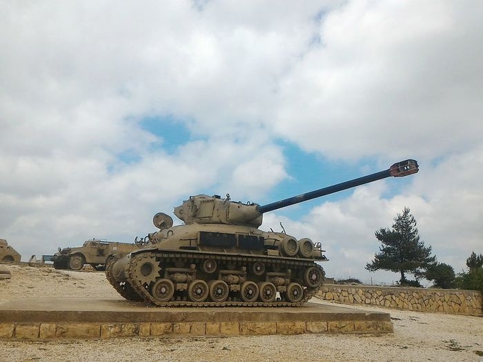 Armored tank against cloudy sky