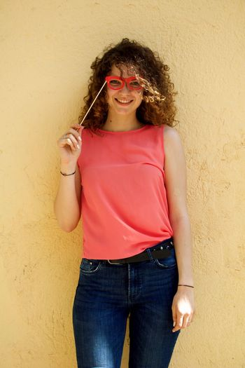Portrait of smiling young woman holding eye mask prop while standing against wall