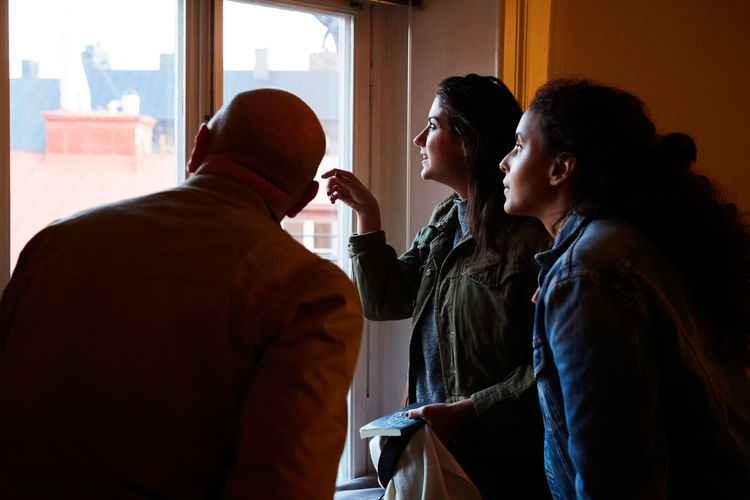 Side view of young couple looking at window