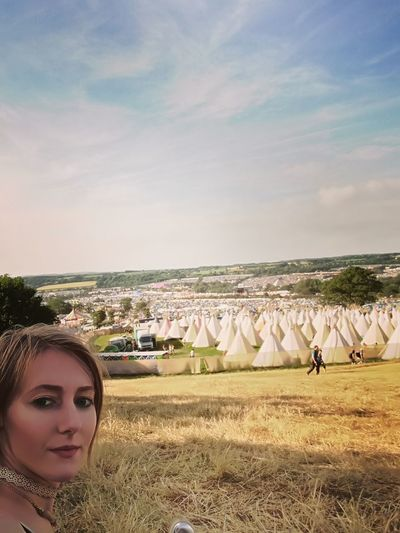 Portrait Of Woman On Teepee Field Against Cloudy Sky During Glastonbury Festival