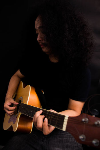 Man playing guitar over black background