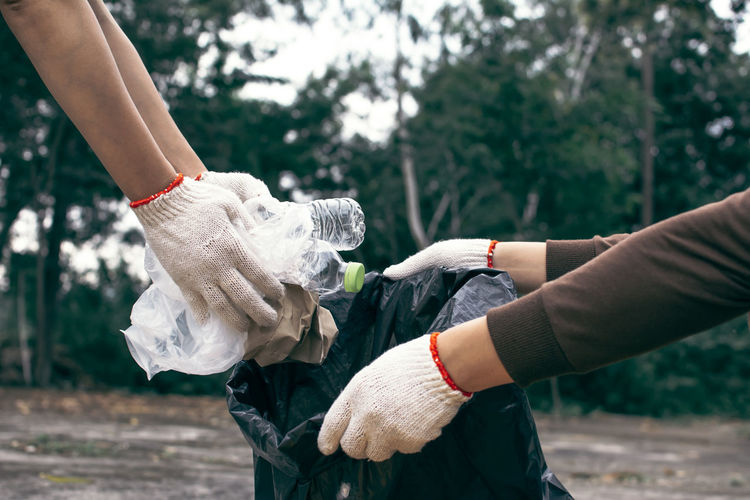 Cropped Hands Collecting Garbage In Plastic Bag On Road