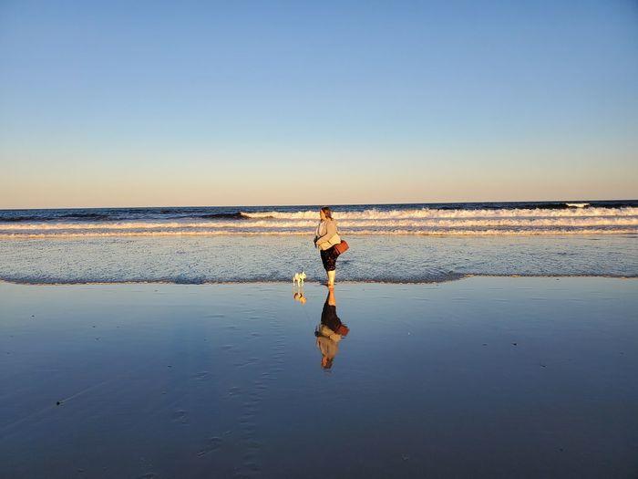 Man on beach against clear sky
