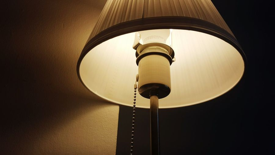 Low angle view of illuminated electric lamp at home