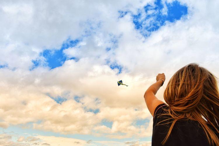 Girl flying kite against sky