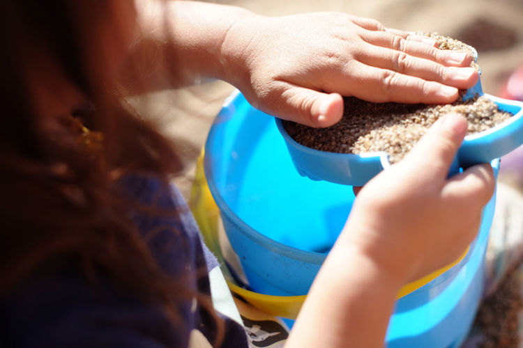 Young girl playing with sand Bucket California Child Childhood Children Close-up Day Food Freshness Holding Human Body Part Human Hand Lifestyles One Person Outdoors Pacific Northwest  Real People Sand USA