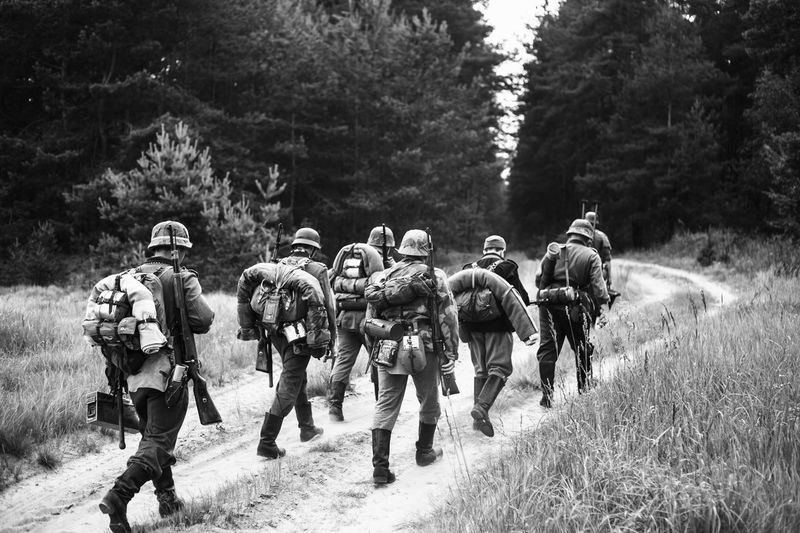 Unidentified re-enactors dressed as World War II German soldiers walks on forest road. Black and white photography Army Battle Front War Patriotic Ww2 WWII Ww1 Millitary German Reenactmant Weapon Historical Uniform Gun Group Of People Helmet Forest Road Re-enactment