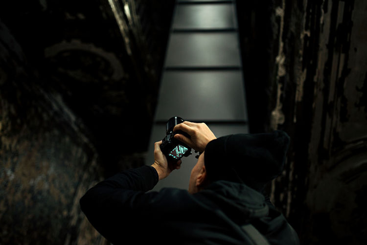Low angle view of young man photographing with camera at night
