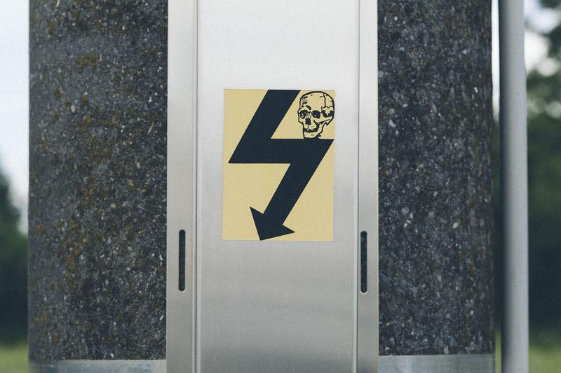 Close-up of danger sign with human skull on electric pole