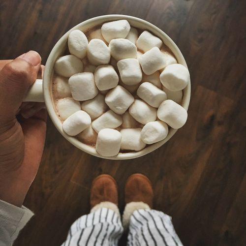 Hand holding marshmallows in cup