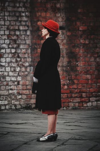 Side view of woman standing on footpath against brick wall
